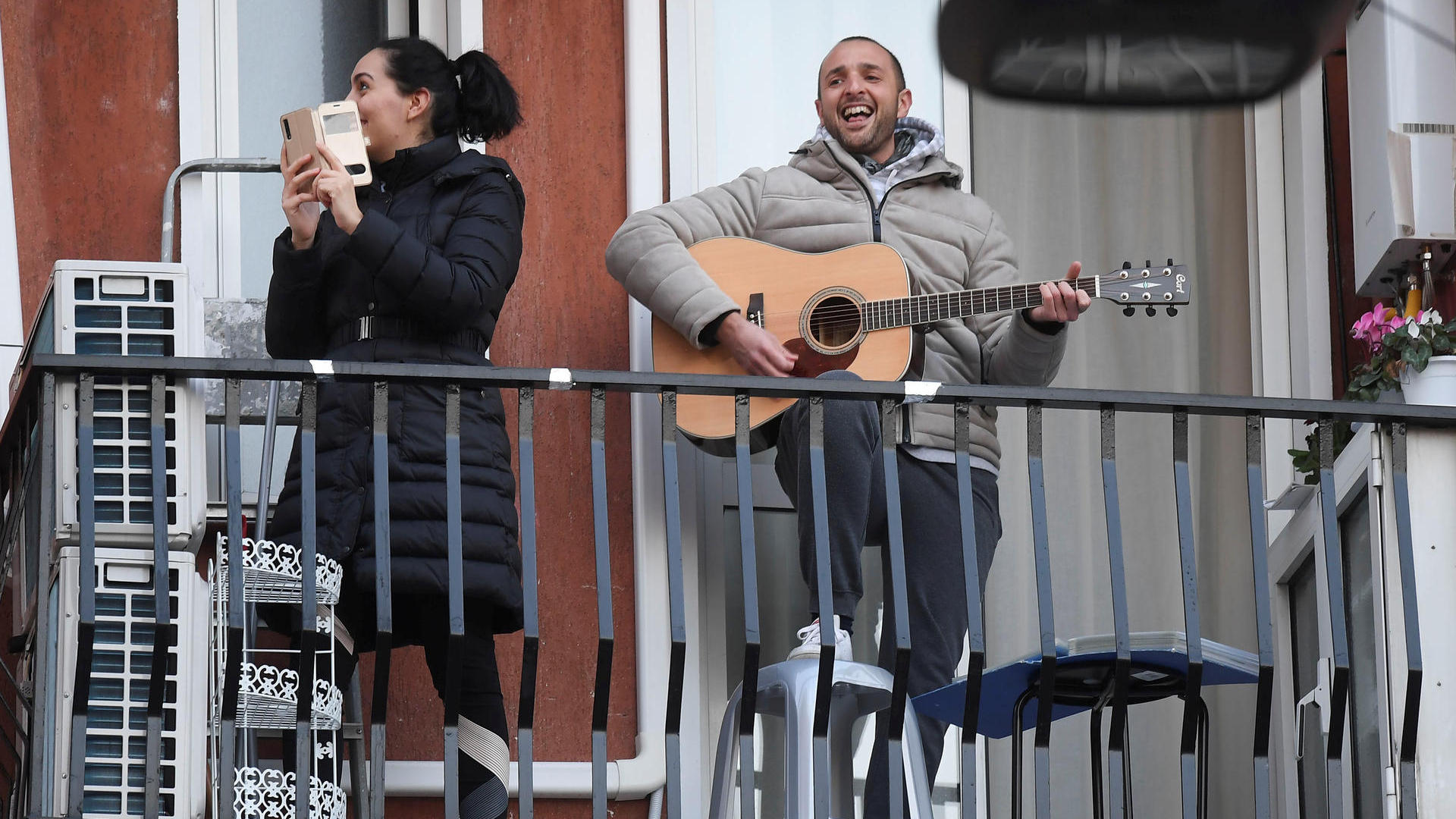 ein mann spielt gitarre auf dem balkon musik bringt menschen in zeiten der corona krise zusammen